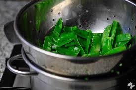 Gekookte peulen afgieten en dan een klontje boter erbij